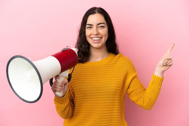 Młoda kaukaska kobieta na różowym tle krzyczy przez megafon i wskazuje bok and