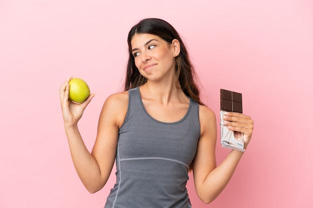 Młoda kaukaska kobieta na różowym tle ma wątpliwości, biorąc w jedną rękę tabliczkę czekolady, a w drugiej jabłko
