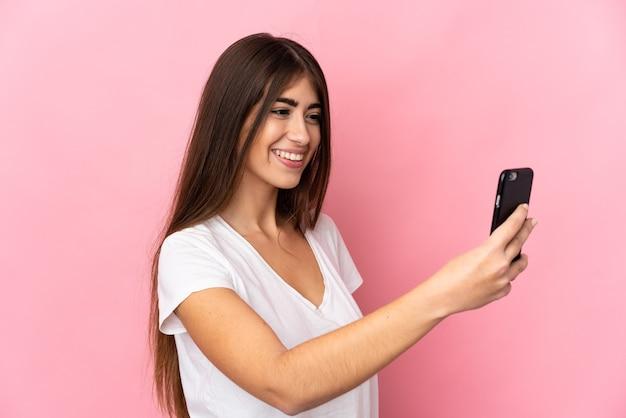 Młoda kaukaska kobieta na różowym tle robi selfie z telefonem komórkowym