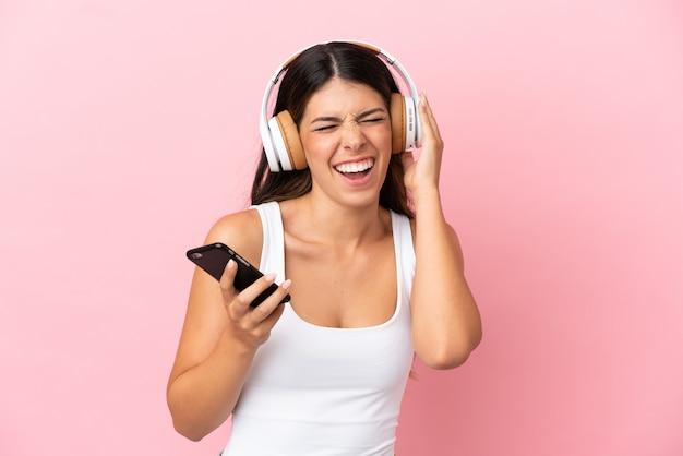 Młoda kaukaska kobieta na różowym tle słucha muzyki za pomocą telefonu komórkowego i śpiewa