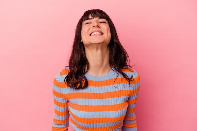 Młoda kaukaska kobieta na różowym tle śmieje się i zamyka oczy, czuje się zrelaksowana i szczęśliwa.