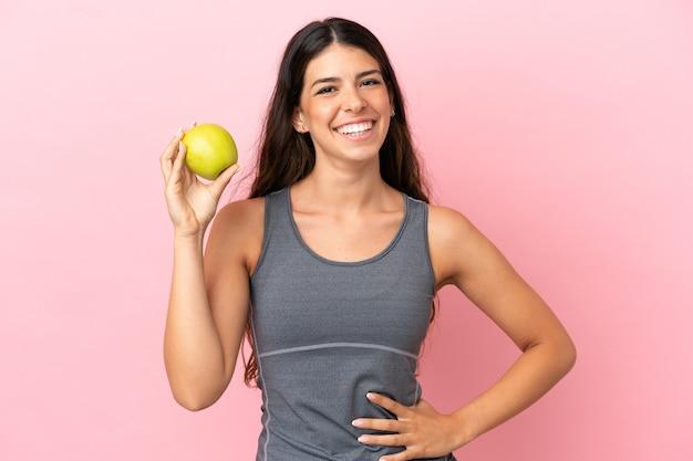 Młoda kaukaska kobieta na różowym tle z jabłkiem i szczęśliwa