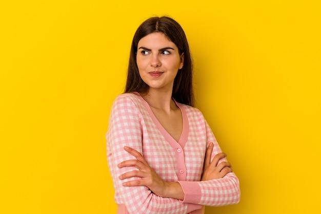 Młoda kaukaska kobieta na żółtym tle marząca o osiągnięciu celów i celów