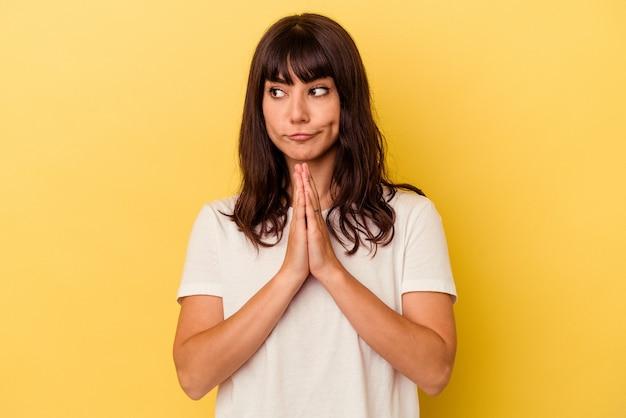 Młoda kaukaska kobieta na żółtym tle modląca się, okazująca oddanie, osoba religijna szukająca boskiej inspiracji.