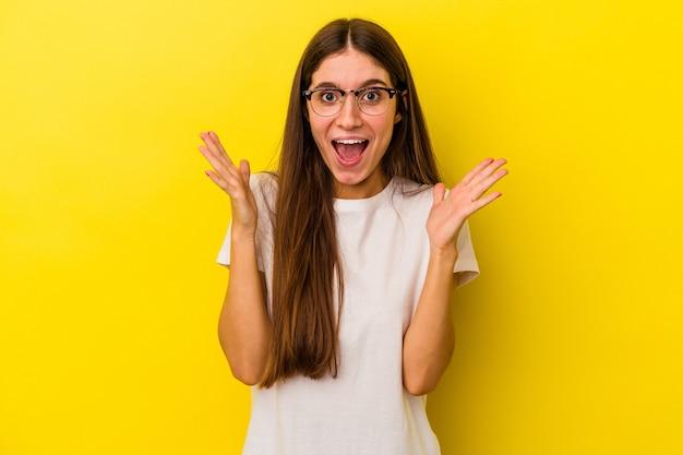 Młoda kaukaska kobieta na żółtym tle świętuje zwycięstwo lub sukces, jest zaskoczony i zszokowany.