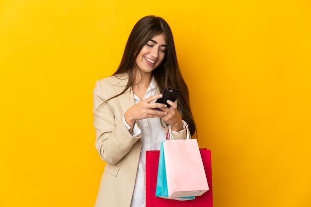 Młoda kaukaska kobieta na żółtym tle trzyma torby na zakupy i pisze wiadomość telefonem komórkowym do przyjaciela