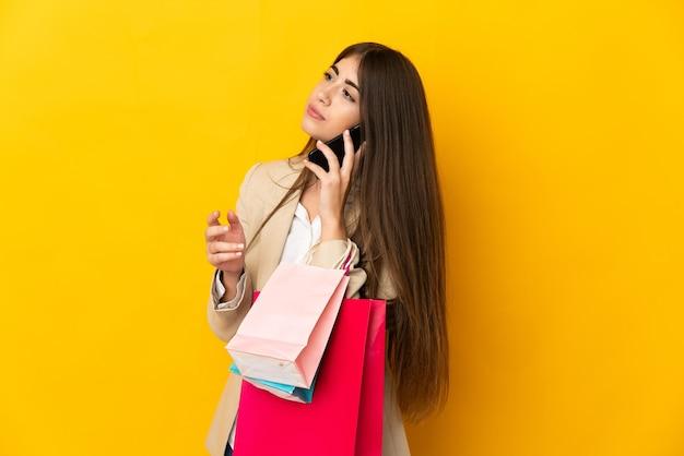 Młoda kaukaska kobieta na żółtym tle trzymająca torby na zakupy i dzwoniąca do przyjaciela za pomocą telefonu komórkowego