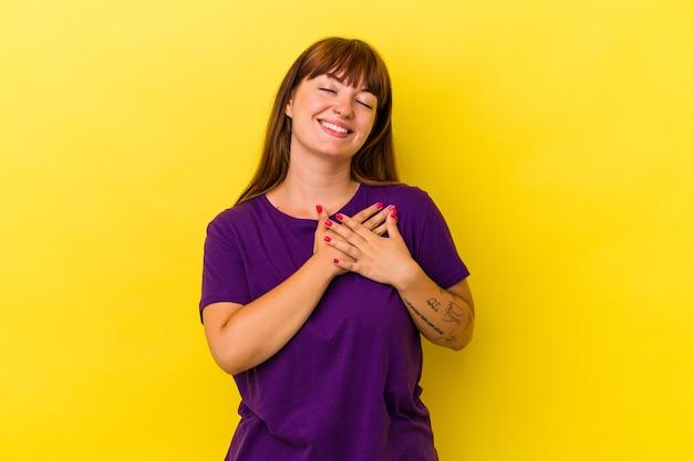 Młoda kaukaska kobieta o krągłych kształtach na żółtym tle ma przyjazny wyraz, przyciskając dłoń do klatki piersiowej. koncepcja miłości.