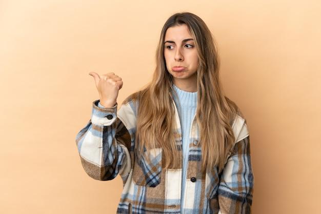Młoda kaukaska kobieta odizolowana na beżowym tle nieszczęśliwa i wskazująca na bok