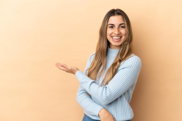Młoda kaukaska kobieta odizolowana na beżowym tle prezentuje pomysł, patrząc w kierunku uśmiechu