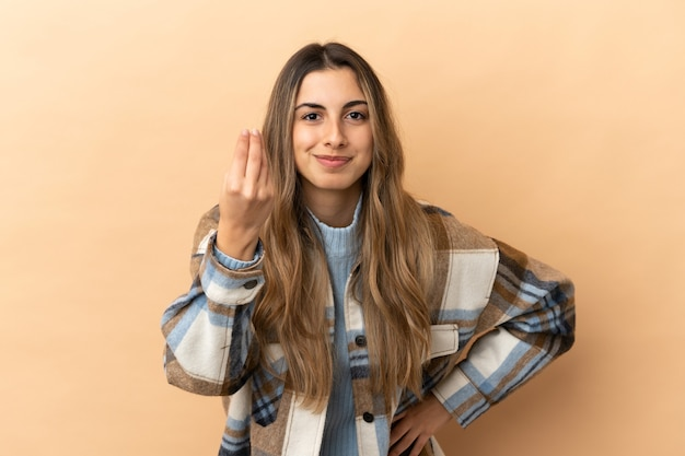 Młoda kaukaska kobieta odizolowana na beżowym tle wykonująca włoski gest