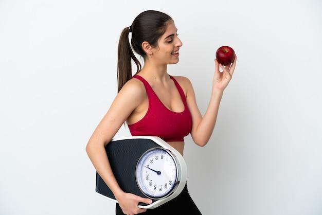 Młoda kaukaska kobieta odizolowana na białej ścianie z wagą i jabłkiem