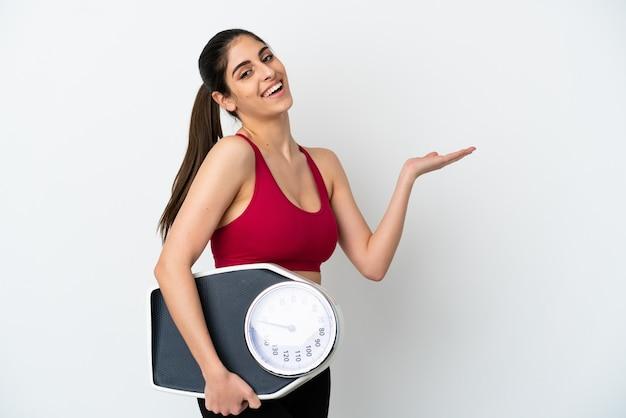 Młoda kaukaska kobieta odizolowana na białej ścianie z wagą