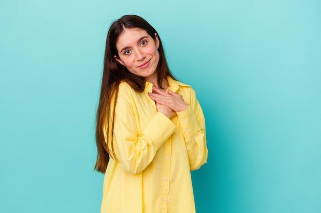 Młoda kaukaska kobieta odizolowana na niebieskiej ścianie ma przyjazny wyraz twarzy, przyciskając dłoń do piersi. koncepcja miłości.
