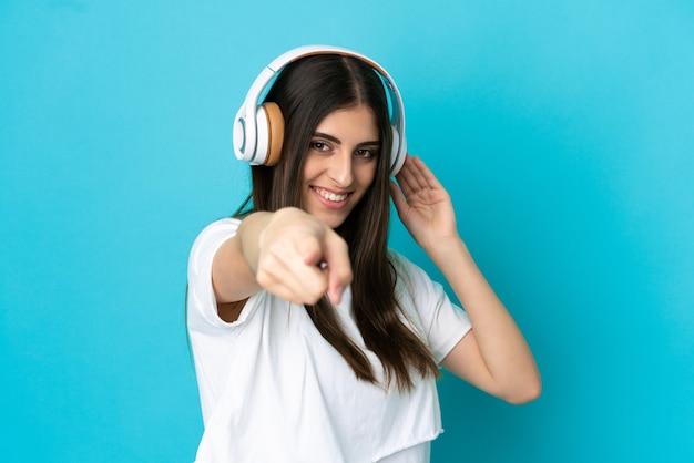 Młoda kaukaska kobieta odizolowana na niebieskim tle słuchająca muzyki i wskazująca do przodu