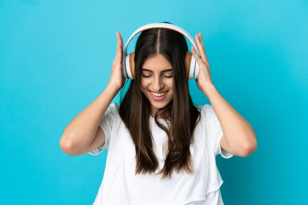 Młoda kaukaska kobieta odizolowana na niebieskim tle słuchania muzyki