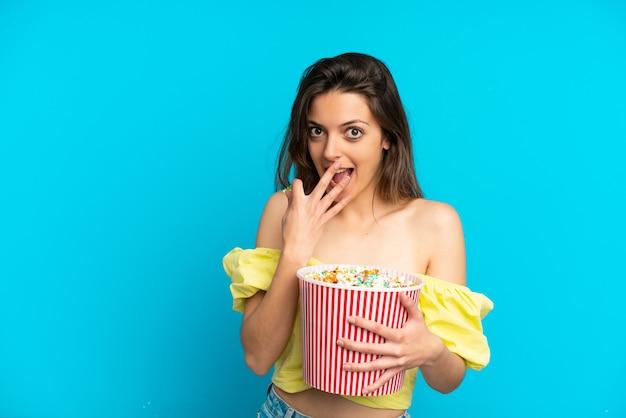 Młoda kaukaska kobieta odizolowana na niebieskim tle trzymająca duże wiadro popcornów