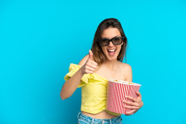 Młoda kaukaska kobieta odizolowana na niebieskim tle w okularach 3d i trzymająca duże wiadro popcornów, wskazując przód