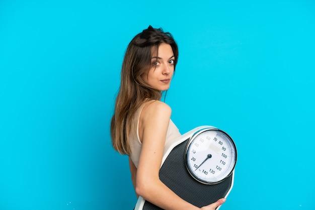 Młoda kaukaska kobieta odizolowana na niebieskim tle z maszyną do ważenia