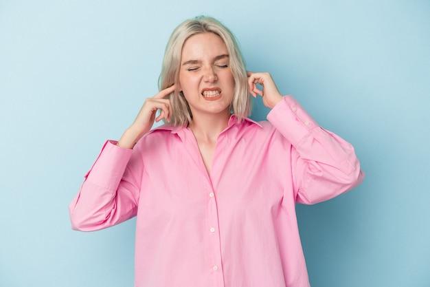 Młoda kaukaska kobieta odizolowana na niebieskim tle zakrywająca uszy palcami, zestresowana i zdesperowana głośnym otoczeniem.
