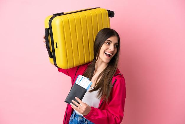 Młoda kaukaska kobieta odizolowana na różowej ścianie na wakacjach z walizką i paszportem