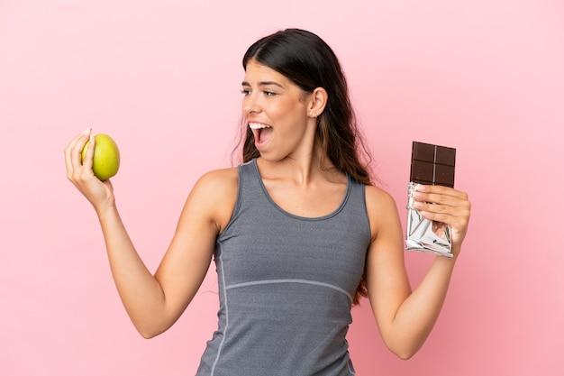 Młoda kaukaska kobieta odizolowana na różowym tle bierze w jedną rękę tabliczkę czekolady, a w drugiej jabłko