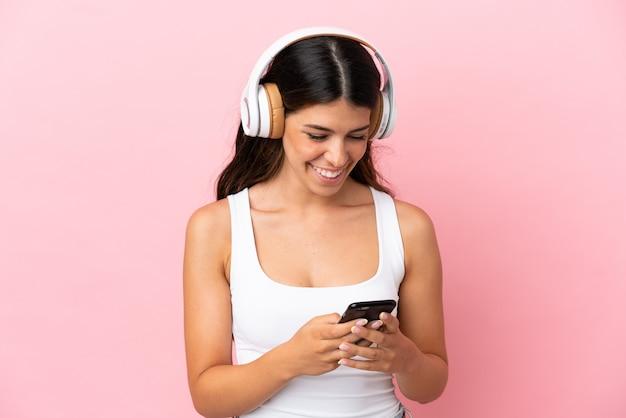Młoda kaukaska kobieta odizolowana na różowym tle słuchająca muzyki i patrząca na telefon komórkowy