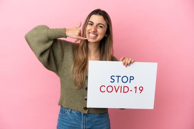 Młoda kaukaska kobieta odizolowana na różowym tle trzyma afisz z tekstem stop covid 19 i robi gest telefoniczny