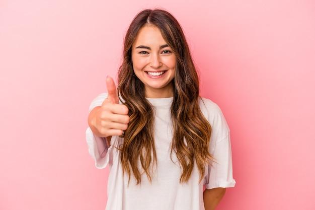 Młoda kaukaska kobieta odizolowana na różowym tle uśmiecha się i podnosi kciuk w górę