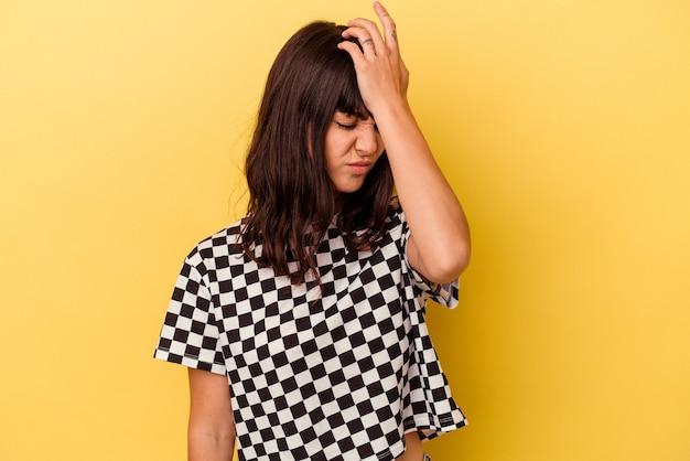 Młoda kaukaska kobieta odizolowana na żółtej ścianie zapominając o czymś, uderzając dłonią w czoło i zamykając oczy.