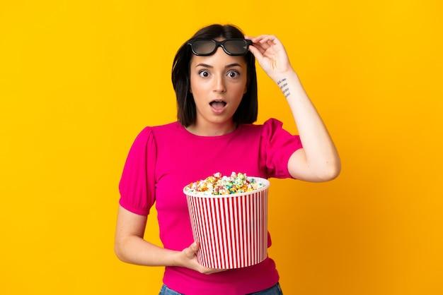 Młoda kaukaska kobieta odizolowana na żółtej ścianie zaskoczona okularami 3d i trzymająca duże wiadro popcornu