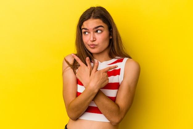 Młoda kaukaska kobieta odizolowana na żółtym tle wskazuje na boki, próbuje wybrać jedną z dwóch opcji.