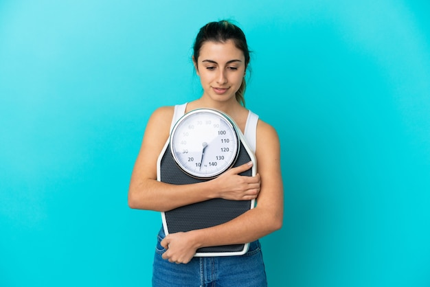 Młoda kaukaska kobieta odizolowana z maszyną do ważenia