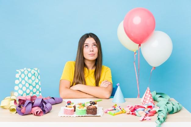 Młoda kaukaska kobieta organizująca urodziny zmęczona powtarzalnym zadaniem.