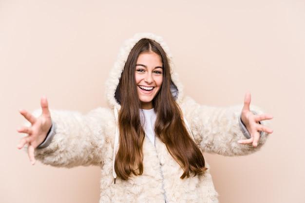 Młoda kaukaska kobieta pozuje na białym tle czuje się pewnie, przytulając aparat.