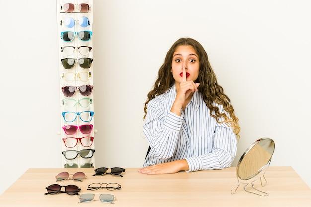 Młoda kaukaska kobieta próbuje okularów na białym tle, zachowując tajemnicę lub prosząc o ciszę