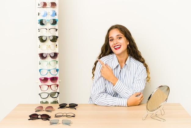 Młoda kaukaska kobieta próbuje okularów, uśmiechając się i wskazując na bok, pokazując coś w pustej przestrzeni.