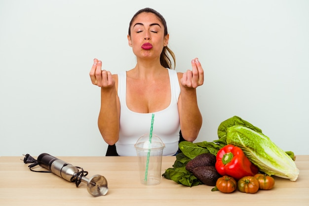 Młoda kaukaska kobieta przygotowuje zdrowy koktajl z warzywami, pokazując, że nie ma pieniędzy.