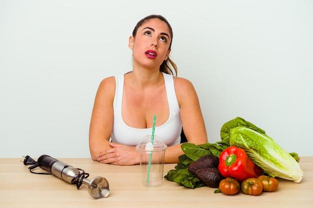 Młoda kaukaska kobieta przygotowuje zdrowy koktajl z warzywami zmęczony powtarzającym się zadaniem.