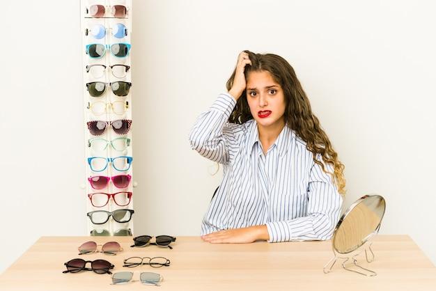 Młoda kaukaska kobieta przymierzająca okulary, wstrząśnięta, przypomniała sobie ważne spotkanie.