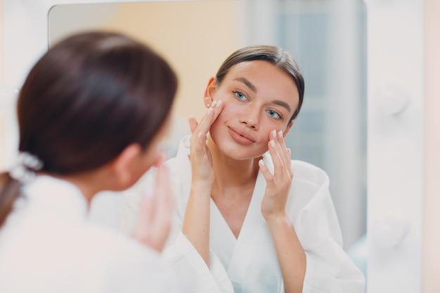 Młoda kaukaska kobieta robi facebuilding joga gimnastyka twarzy self limfatyczny masaż twarzy w domu lustro