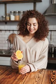 Młoda kaukaska kobieta robi i pije świeży sok pomarańczowy podczas śniadania w kuchni w domu