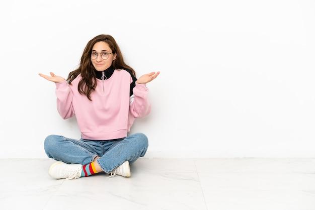 Młoda kaukaska kobieta siedząca na podłodze na białym tle, mająca wątpliwości podczas podnoszenia rąk