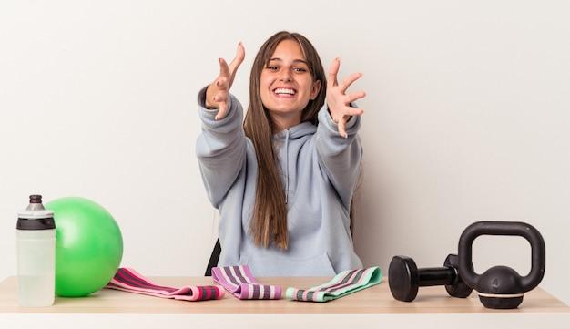 Młoda kaukaska kobieta siedząca przy stole ze sprzętem sportowym na białym tle czuje się pewnie, przytulając się do kamery.