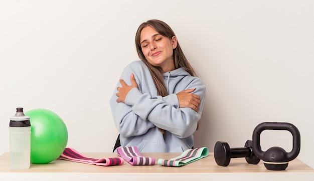 Młoda kaukaska kobieta siedząca przy stole ze sprzętem sportowym na białym tle przytula się, uśmiechając się beztrosko i szczęśliwie.