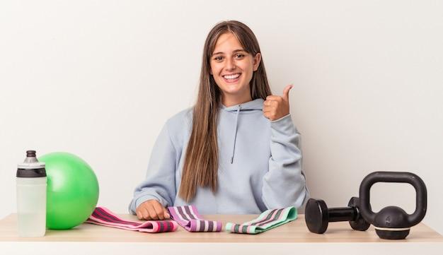 Młoda kaukaska kobieta siedząca przy stole ze sprzętem sportowym na białym tle uśmiechnięta i unosząca kciuk w górę