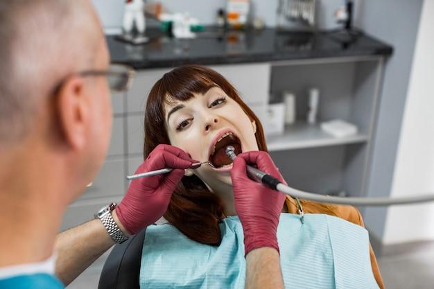 Młoda kaukaska kobieta, siedzący w krześle dentysta, patrzejący kamerę z otwartymi usta podczas gdy doktorski sprawdza zęby.