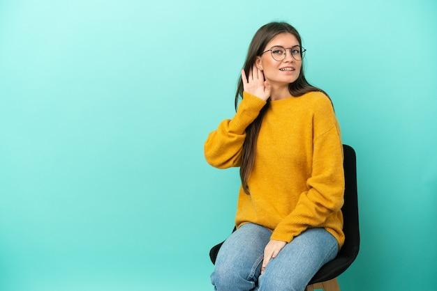 Młoda kaukaska kobieta siedzi na krześle na białym tle na niebieskim tle, słuchając czegoś, kładąc rękę na uchu