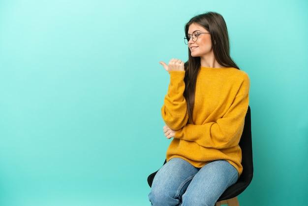 Młoda kaukaska kobieta siedzi na krześle na białym tle na niebieskim tle, wskazując na bok, aby zaprezentować produkt