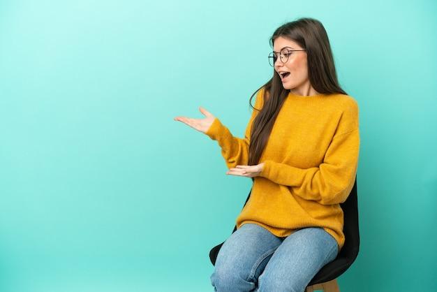 Młoda kaukaska kobieta siedzi na krześle na białym tle na niebieskim tle z niespodzianką wyrazem twarzy